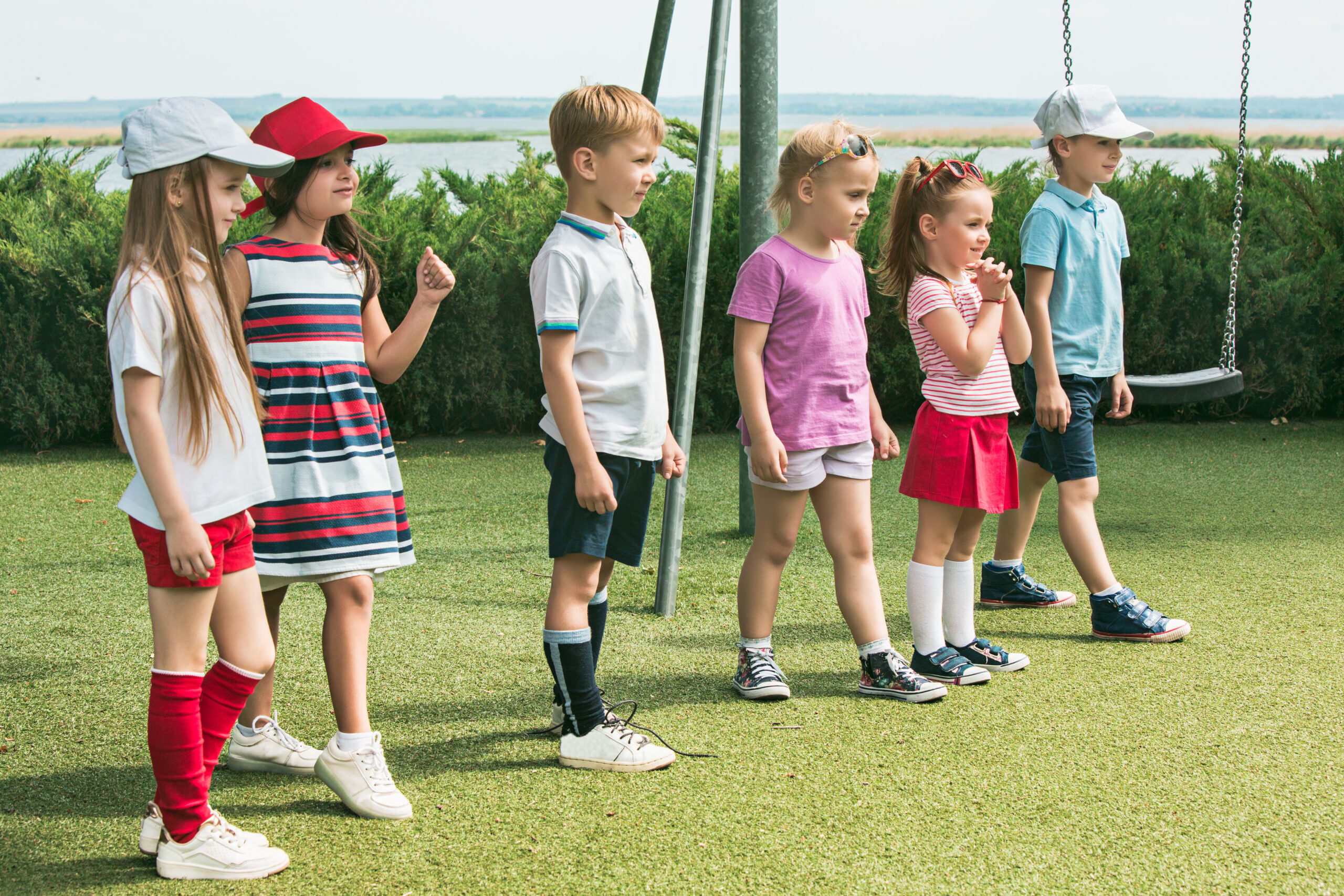 Funny starts. Kids fashion concept. The group of teen boys and girls standing at park. Children colorful clothes, lifestyle, trendy colors concepts.