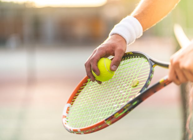 Young Man Playing Tennis Outdoors. Close Up of Tennis Player Hands Holding Racket with Ball. Professional Tennis Player Hitting the Ball. Sport Concept.